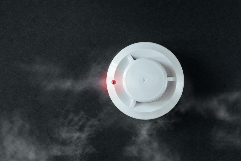 Smoke detector and fire detector on a black background in action surrounded by smoke. Fire alarm on a wall with copy space.