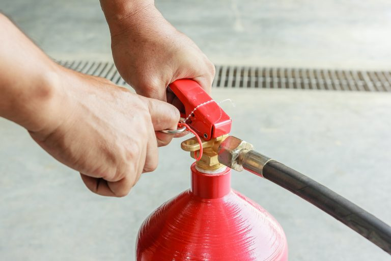 Male hands pulling safety pin of fire extinguisher closeup